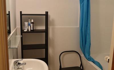 Salle de bains - La salle de bains rénovée, avec baignoire et rangements.